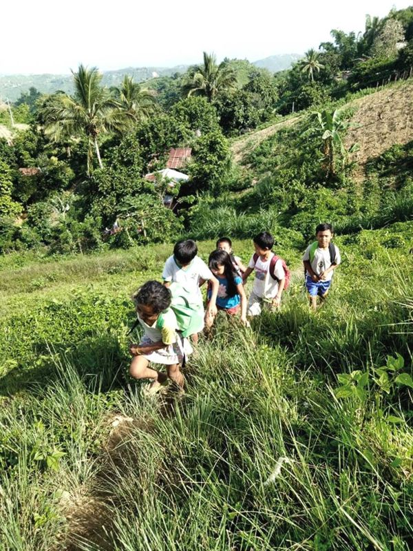 PUPILS' PERSISTENCE.  Students in the mountain village of Calbasaan in Minglanilla, Cebu have to pass through an uphill passage while carrying bags full of books before reaching their school. (CONTRIBUTED FOTO)