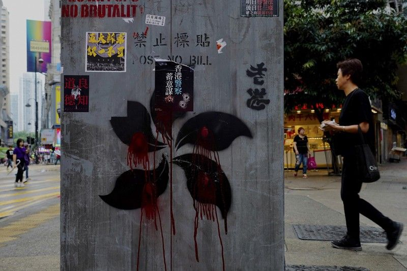 HONG KONG. People walk near graffiti on a pillar which shows Hong Kong Special Administrative Region (SAR) flag pattern drawn in black and red in Hong Kong, Monday, October 7, 2019. Tens of thousands of masked protesters marched defiantly in the city center Sunday, but the peaceful rallies quickly degenerated into chaos at several locations as hard-liners again lobbed gasoline bombs, started fires and trashed subway stations and China-linked banks and shops. (AP)