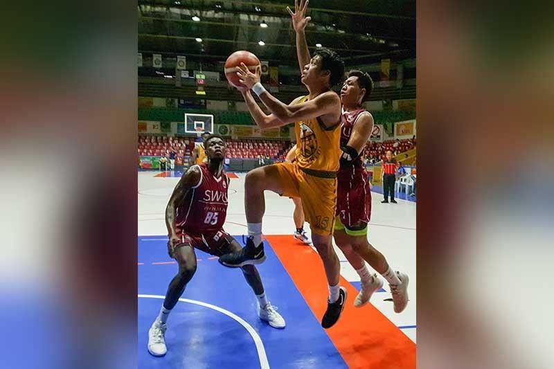 NABIYAAN: Si Justine Jules Langres, tunga, sa University of San Carlos (USC) Warriors nga milusot atubangan sa duha ka Cobras sa Southwestern University-Phinma nga nagguwardiya kaniya niining aktoha atol sa ilang duwa niadtong Dominggo sa nagpadayon nga Cesafi men's basketball sa Cebu Coliseum. Ang SWU-Phinma mibuntog sa USC Warriors, 66-61, sa maong duwa. (Arni Aclao)