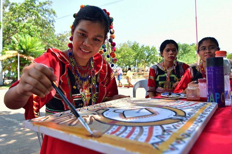PINASAHING PAGPINTA. Gigamitan sa usa ka Matigsalug nga sumasalmot sa painting contest kagahapon ang iyang ginabuhat nga obra ug mga materyales nga makita sa ilang lona sa bukid sama sa kape, kamatis, lapok, achuete, ug atsal atol aktibidades sa 3rd Davao City Indigenous People's Youth Artists' Assembly kagahapon sa Magsaysay Park, Davao City. (Macky Lim)