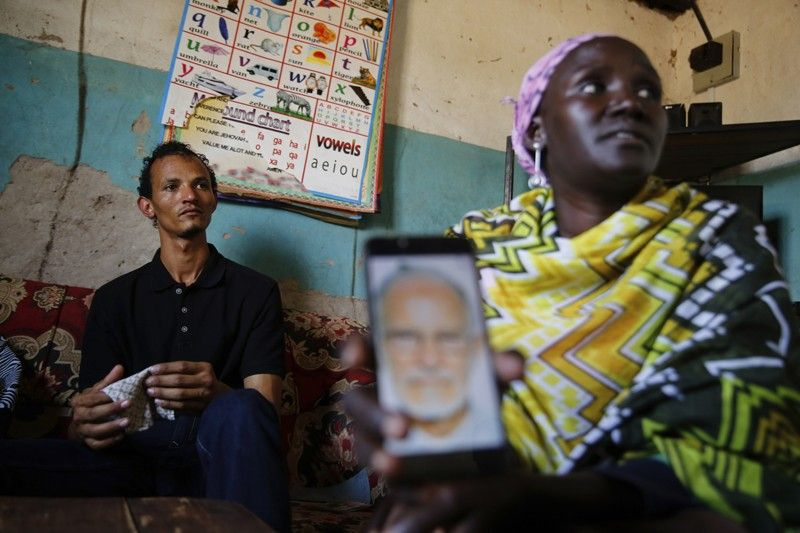 "KENYA. Gerald Erebon sits with his aunt, Scolastica Apayo, as she holds a phone displaying a photo of the Reverend Mario Lacchin, during an interview at her home in the Isiolo area of the Archers Post settlement in Kenya on Sunday, June 30, 2019. Scolastica said her sister, Sabina Losirkale, finally told her the secret in 2012, two weeks before she died. ""Now that my days are over,"" her sister told her, she could reveal all: ""When Gerald will ask you who's his father, just tell him: Father Mario."" (AP)"