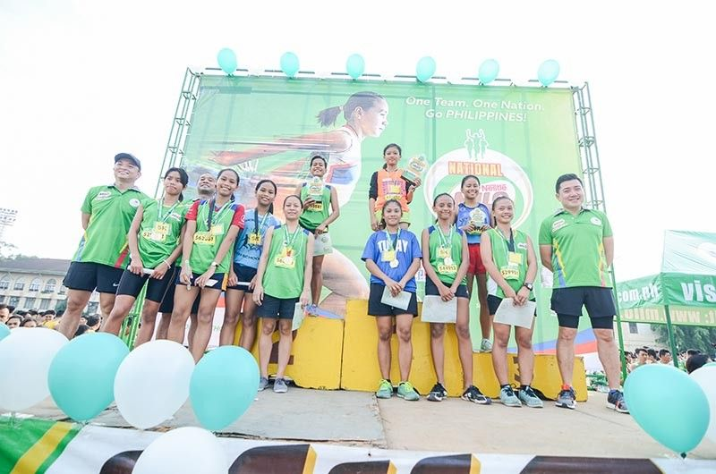 INSPIRA-TION. With the picture of her idol Mary Joy Tabal right behind her, 12-year-old Asia Abucay Paraase receives her trophy for winning in the women's 5K division in the Milo Marathon Cebu leg. (Contributed Photo)