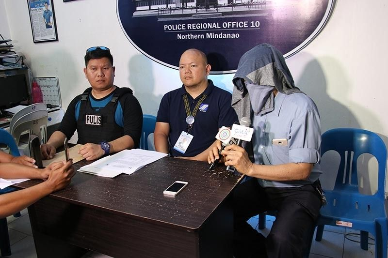 CAGAYAN DE ORO. Police arrested businessman Bienvenido Macaraeg Jr., for non-remittance of SSS contributions. In the photo, Macaraeg covers his face with a shirt while telling the media he was unable to pay because a fire engulfed his store, and accused his employees of stealing from him. (Photo courtesy of PRO-10)