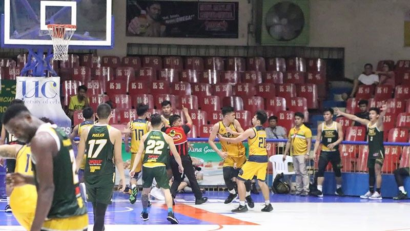 CEBU. USPF forward Steven Ursal tries to get away from the bench area of USC after he and Warriors forward Kenneth Brillo figured in a commotion. (Amper Campaña)