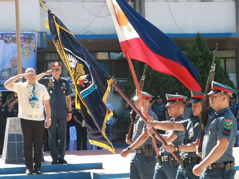 PAMPANGA. Representative Jorge Antonio Bustos of Patrol Party-list and Police Colonel Joyce Patrick Sangalang salute the Philippine flag and colors during Monday's (October 7) parade of troops and flag raising at the Angeles City Police Office. (Chris Navarro)