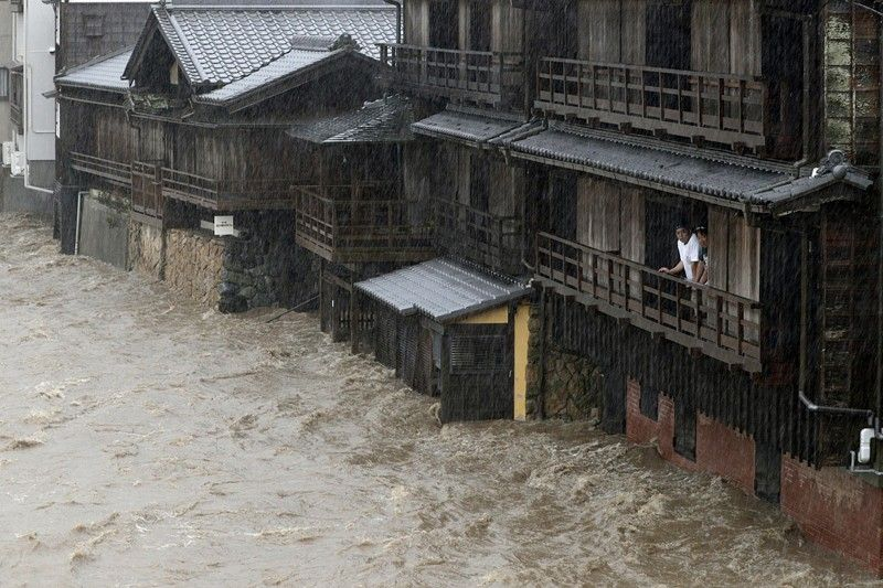 JAPAN. People watch the Isuzu River swollen by Typhoon Hagibis, in Ise, central Japan Saturday, October 12, 2019. Tokyo and surrounding areas braced for a powerful typhoon forecast as the worst in six decades, with streets and trains stations unusually quiet Saturday as rain poured over the city. (AP)