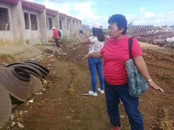 """EASTERN SAMAR. Lita Bagunas, Yolanda survivor and leader from Community of Yolanda Survivors and Partners (CYSP), points to the housing units in Giporlos, Eastern Samar, which they claimed as """"too small, too hot, and substandard"""". (Ronald O. Reyes/File photo)"""