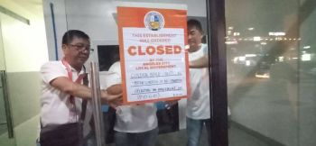 PAMPANGA. Personnel of the Business Permit and Licensing Division (BPLD) of Angeles City post a sign announcing the closure of Golden Build Limited Incorporated. (Contributed Photo)