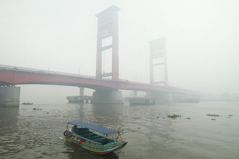 INDONESIA. A boat motors through thick haze from forest fires blanket Ampera Bridge in the background in Palembang, South Sumatra, Indonesia, Monday, October 14, 2019. Thick, noxious haze from new deliberately set fires blanketed parts of Indonesia's Sumatra island on Monday after days of improving air quality, causing school closings and flight delays. <b>(AP)</b>