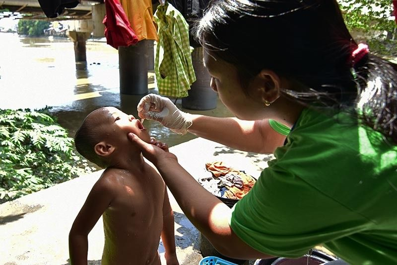 DAVAO. A young boy takes a short break from his morning bath as barangay health workers arrive outside their house in Barangay 5-A, Bankerohan Riverside to give oral polio vaccine to children five years old and below. The health workers conducted a house-to-house vaccination in line with the Sabayang Patak Kontra Polio launching in Davao City Monday, October 14, 2019. (Macky Lim)