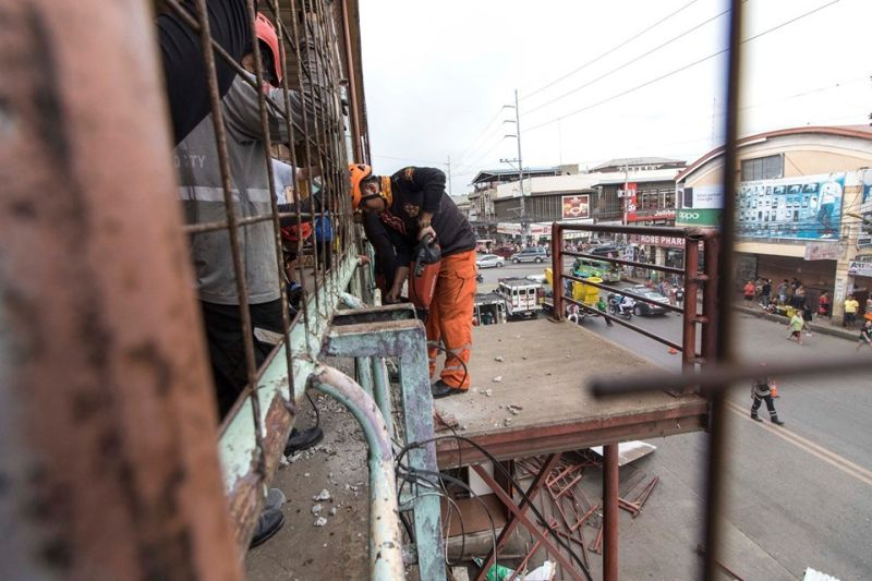 CAGAYAN DE ORO. Members of the road clearing team remove a stairway and a canopy that obstruct the sidewalk in Cogon market, Sunday. (Photo courtesy of CIO)