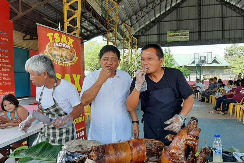 PAMPANGA. Barangay San Juan (City of San Fernando) Chairman Claro Tolentino and Tsax Lechon owner Narciso Tuazon feast on pork lechon to dispel the ASF scare in the community. (Princess Clea Arcellaz)