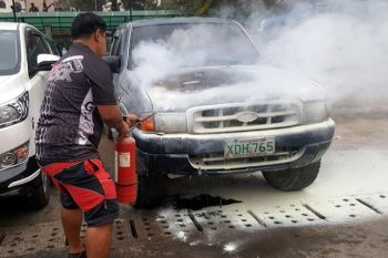 BAGUIO. Residents extinguish fire out of a pick-up truck parked at the Ganza area along Harrison road Sunday afternoon, October 1, 2019. (Jean Nicole Cortes)
