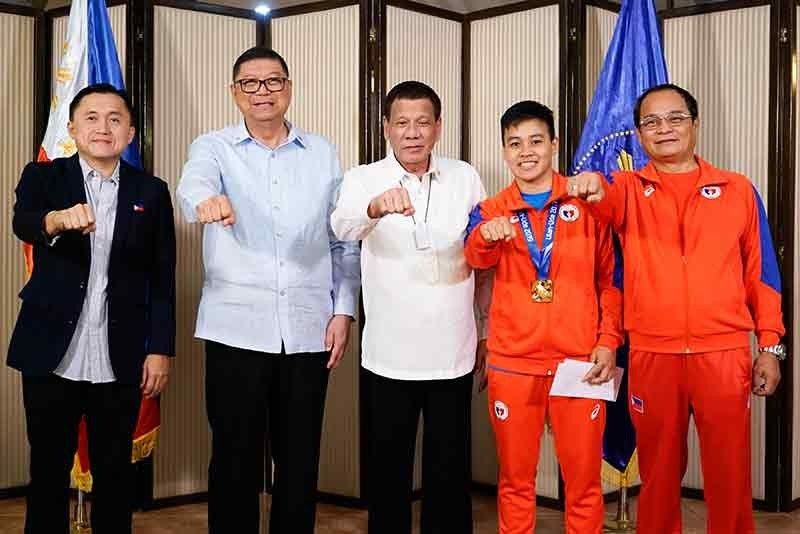 SIGNATURE POSE. President Rodrigo Roa Duterte strikes his signature pose with 2019 AIBA Women's World Boxing Championships Gold Medalist Nesthy Petecio during their meeting at the Malago Clubhouse in Malacañang on October 16, 2019. Also in the photo are Senate Committee on Sports Chair Senator Christopher