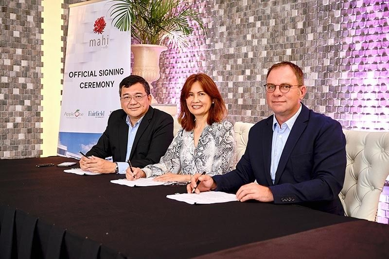 SEALED. From left, couples Ray and Venus Manigsaca of AppleOne Properties Inc. and Steve Baek  (right), Marriott International senior director, forge a new partnership to operate the 198-room Fairfield Inn & Suites in Lapu-Lapu City.(Contributed Photo)