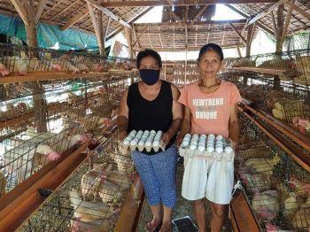 MGA LIDER SA GRUPO: Sila si Remily M. Daniel (wala), Presidente ug Angelita Balud (tuo), Treasurer sa Cang-asa ug Cang-atuyom Sustainable Livelihood Program (SLP) Association sa Barangay Cang-asa, Siquijor, Siquijor sa ilang poultry farm. (Tampo)