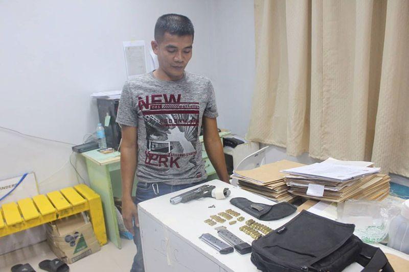 DAVAO. Ang suspek nga bodyguard gihulagwayan sa kapulisan agi'g proseso dihang nasikop kini og nakuhaan og armas ug daghang bala. (PRO-Davao photo)