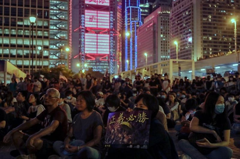 HONG KONG. A woman holds a placard which reads