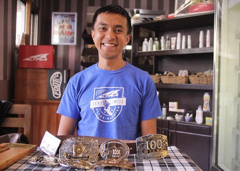 BENGUET. Runner Jovencio Luspian from Mankayan, Benguet shows some of his buckles he gained competing in several ultratrail running event. He said trail running has helped him change his lifestyle. (Photo by Lauren Alimondo)