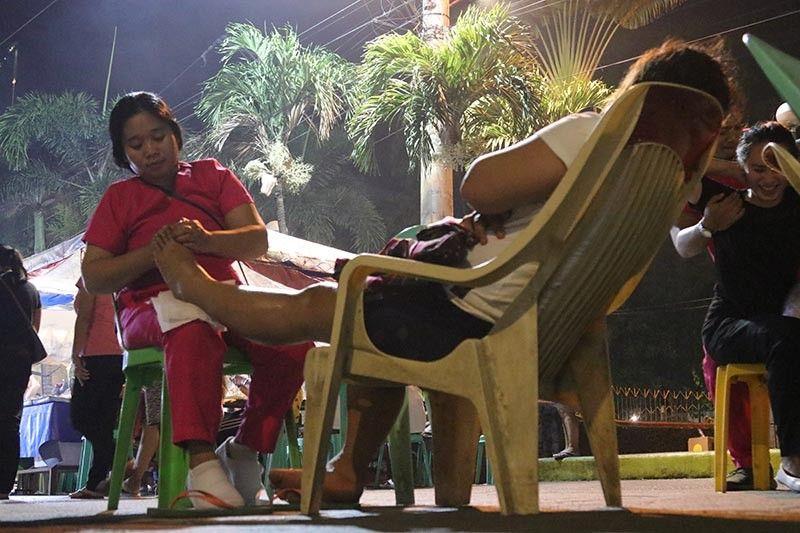 Gi-ayo og hilot sa usa ka masahista ang tiil sa iyang kustomer sa Roxas Night Market, Siyudad sa Davao sa milabay nga gabii. Kini nga eksena maoy sagad makita sa dapit diin asa nagtapok ang mga masahista nga maoy ilang nahimong panginabuhian. (Mark Perandos)