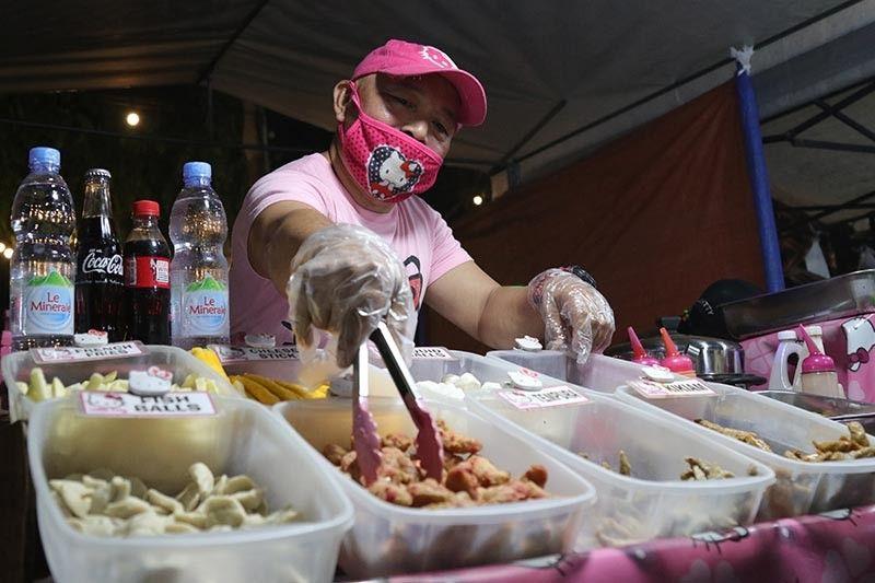 Kompleto nga gisuot sa usa ka tindero sa Roxas Night Market sa Davao City ang iyang uniporme apil na ang plastic gloves sa iyang pagpaninda. Ang kompleto nga uniporme sa pagpaninda usa ka sanitation requirement sa lokal nga kagamhanan sa siyudad aron masiguro nga hinlo ang pag-andam sa pagkaon nga gitinda diha sa publiko. (Mark Perandos)