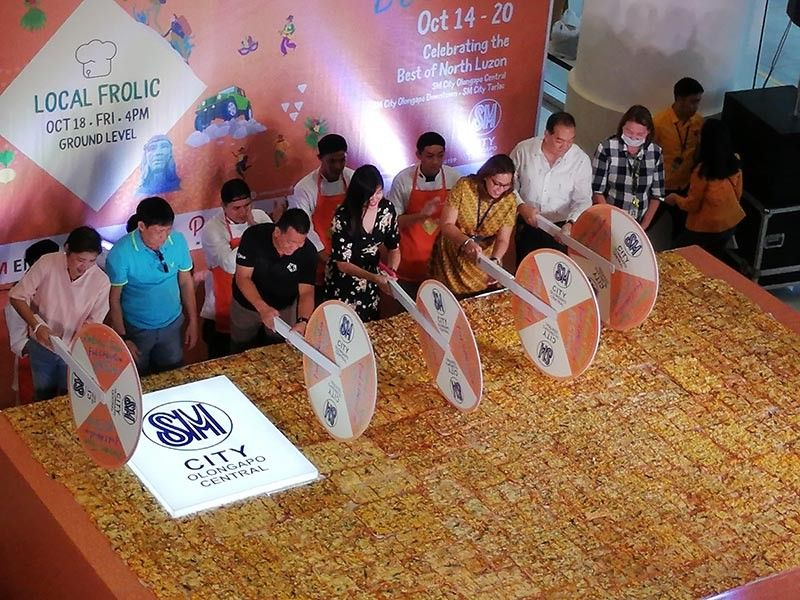 (From left) Olongapo City Councilors Lugie Lipumano, Jerome Bacay, Rodel Cerezo, Kaye Legaspi, SM Olongapo Central Mall manager Ana Lorraine Azucena, Metro Olongapo Chamber of Commerce president Ruben De Guzman and City Tourism head Fifi Legaspi joined together to slice the giant mango pizza at SM City Olongapo Central. The giant pizza was baked and prepared by Lyceum of Subic Bay and Gordon College HRM students. (Contributed photo)
