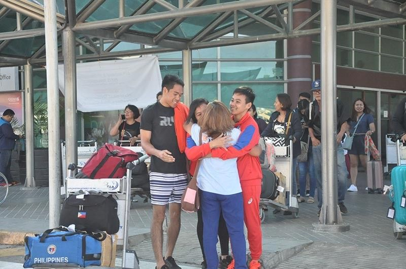 WELCOME BACK. Aiba Women's World Boxing Championships 2019 gold medalist Nesthy Alcayde and sister Nice Zzaa Petecio, both members of the national boxing team, are embraced by their mother Prescilla upon arriving at the Francisco Bangoy International Airport in Davao City yesterday. (Roberto Gubma, Jr.)