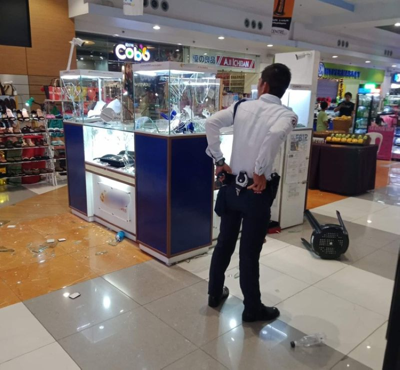 One of the security guards of JCentre Mall, shown here in a photo provided by a netizen, surveys one of the four outlets that were robbed by 15 armed men last Saturday, Oct. 19, 2019. The guard in the photo along with his colleagues on-duty at that time will be subjected to an investigation by the Police Regional Office-Central Visayas (PRO 7). (Contributed foto/Tom Joshua Seno)
