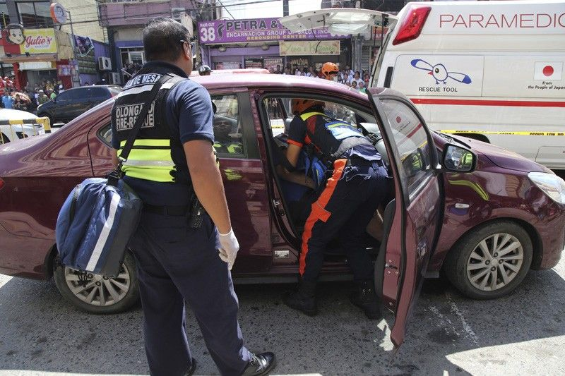 PHILIPPINES. In this October 18, 2019, handout photo provided by the Olongapo Public Information Office, rescue workers check on an Australian named Anthony George inside a car in Olongapo, northern Philippines. Philippine police city director of Olongapo city said they arrested Australian Michael McLaren shortly after the incident for the alleged killing of George and Filipino Mila Bailey inside the car. Another Australian victim, Wayne Bailey, is still recovering at the hospital from gunshot wounds. (AP)