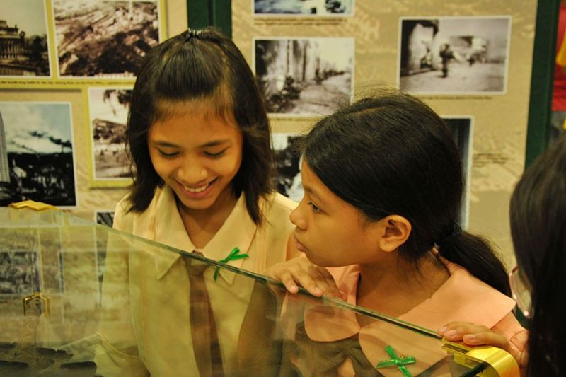 "HISTORY LEARNERS. Two young students visit the exhibit of Philippine Veterans Bank entitled ""The War of Our Fathers"" at Robinsons Mall Tacloban. (Contributed photo)"