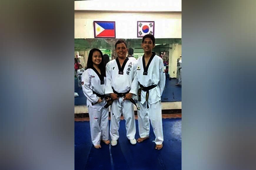 CAGAYAN DE ORO. Melissa Maxine and Kyle George flank their father/trainer George Arsenal after a previous training session at a family-run taekwondo gym in Cagayan de Oro. (Contributed Photo)