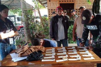 DAVAO. Makita ang suspek (tunga) atol sa gihimong inventory sa mga ebidensiya nga nakuha sa iyang posisyon sa pag-agi niini sa Sirawan checkpoint. (Toril PNP photo)