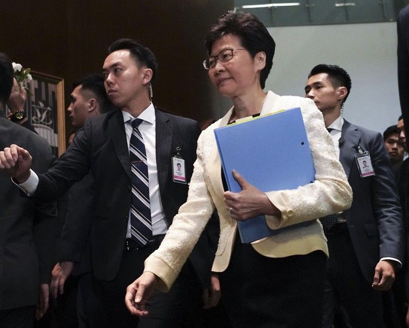 HONG KONG. In this October 17, 2019, file photo, Hong Kong Chief Executive Carrie Lam, center, arrives at chamber of the Legislative Council in Hong Kong. Hong Kong is feuding with Taiwan over a fugitive murder suspect whose case indirectly sparked the protests in Hong Kong over an extradition bill. Hong Kong officials pleaded on Tuesday, October 22, for authorities in Taiwan to let the man surrender himself for killing his girlfriend while visiting the self-ruled island last year. (AP)