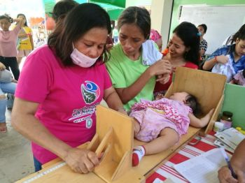 DAVAO. A barangay health worker measures the height of the baby as a requirement for immunization at the health center in Barangay Tibungco, Davao City. The health center also practices a family-friendly environment inside their facility for the parents to enjoy bringing their children to the center. (Mark Perandos)
