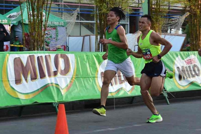 DAVAO. With all the strength he could muster, Rizal Memorial Colleges (RMC) varsity trackster Arlan Arbois, Jr., right, endures sore leg muscles enroute to reaching the finish line and crowning himself 42nd National Milo Marathon Davao Leg male 21K champion at SM Lanang car park in Davao City last Sunday, October 20. (Macky Lim)