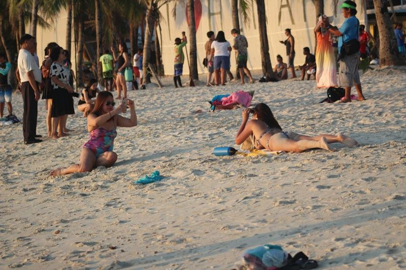 BORACAY ISLAND. Tourists enjoying the scenic view in Boracay. The DTI urged tourists coming to the resort island to patronize green products. (Photo by Jun N. Aguirre)