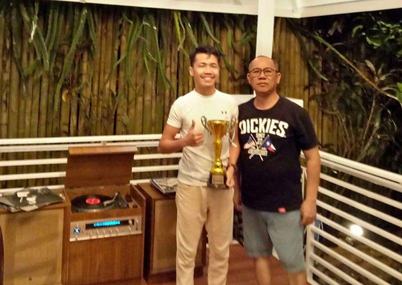CHESS CHAMPION. John Ray Batucan, left, receives the champion's trophy from Jardin del Roca Pool Chess Tournament 2019 presenter and organizer lawyer Jong Guevarra Jr. (Jong Guevarra Jr. Facebook)