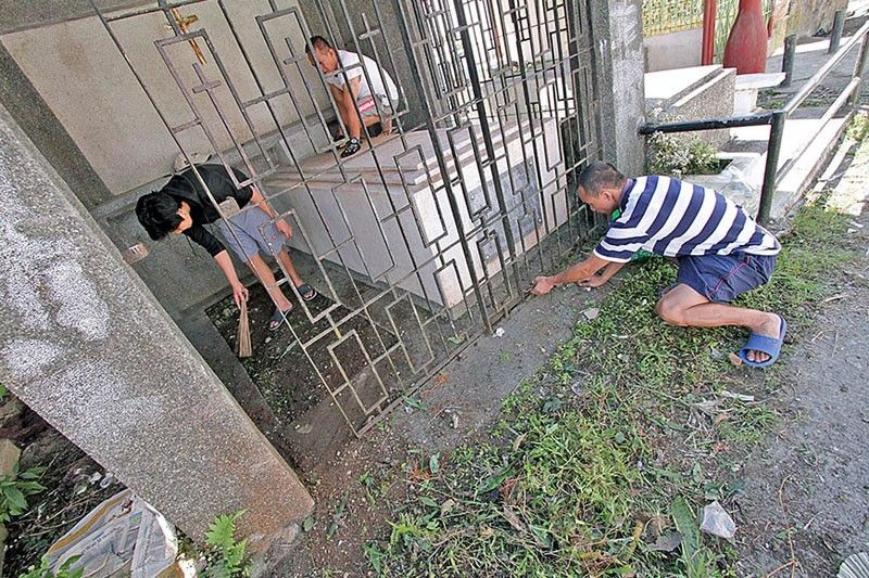 BAGUIO. Relatives of the dearly departed and hired cleaners have started to clean individual plots or family mausoleums in Baguio City Public Cemetery a few days before hordes of visitors start flocking to the cemeteries on November 1, All Saints' Day. (Photo by Jean Nicole Cortes)