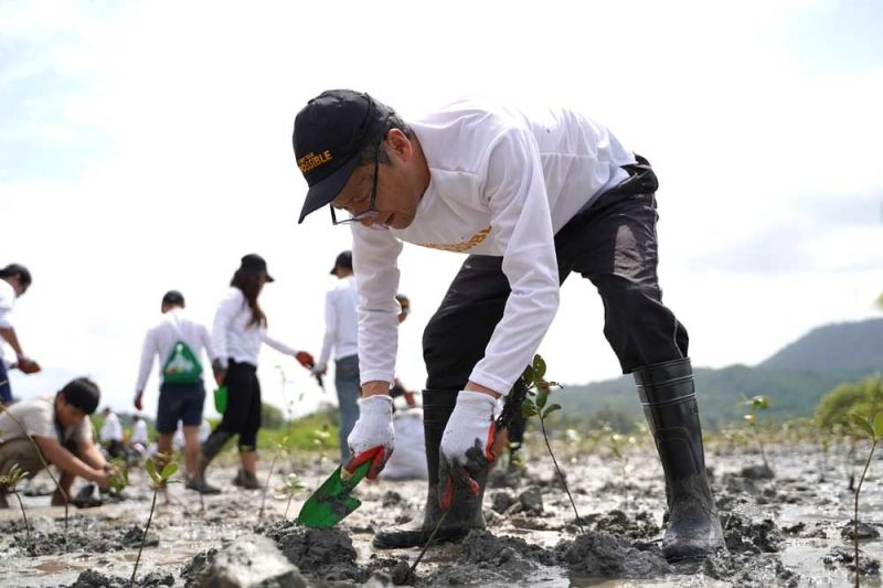 PLANTING LEADERSHIP. Toyota Motor Philippines (TMP) president Satoru Suzuki leads volunteers in planting mangroves in Batangas as part of TMP's Start Your Impossible initiative, which includes projects that protect the environment. (CONTRIBUTED FOTO)