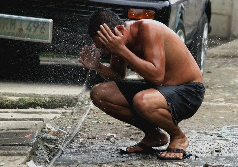 CEBU. In this photo taken on August 13, 2004, a bystander gets a refreshing wash from a leaking water pipe. (File photo)