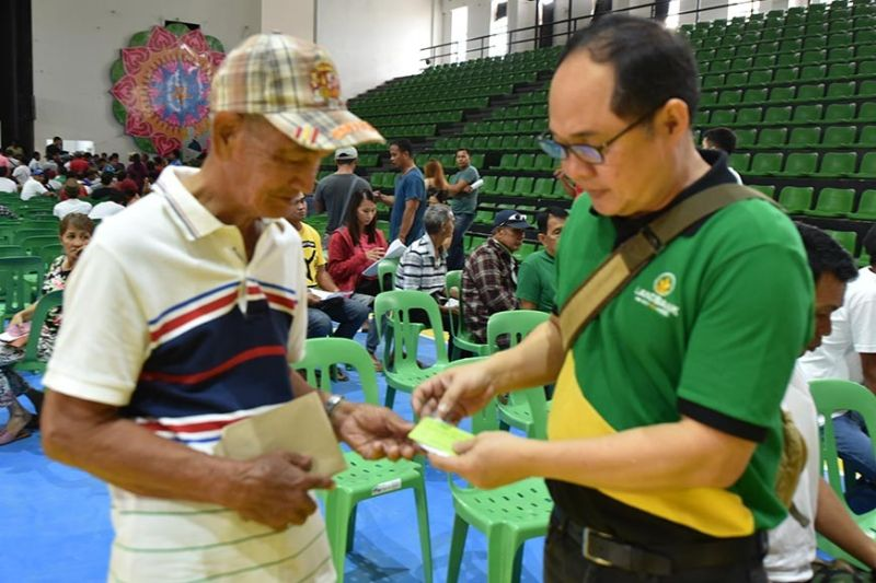PAMPANGA. A staff member from the Pampanga Landbank lending center distributes the cash cards of Sure Aid recipients at the Bren Z. Guiao Convention Center. (Pampanga PIO)