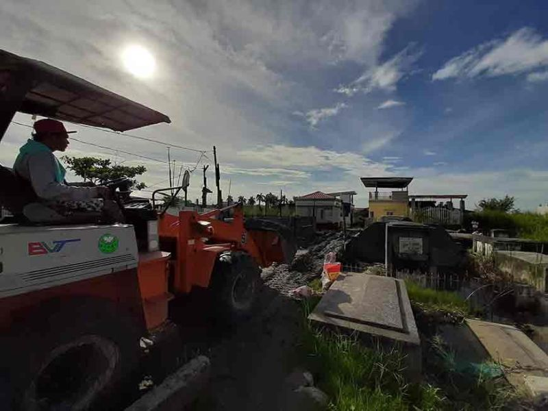 PAMPANGA. A man operates a small backhoe to upgrade the access way in a flooded cemetery in Masantol, Pampanga two days before All Saints' Day. (Princess Clea Arcellaz)