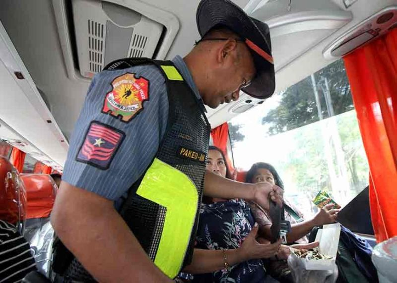 BAGUIO. A highway patrol officer inspects the seatbelts of a bus on Gov. Pack Road to ensure safety and security of passengers traveling to and from Baguio City to observe the All Saints' and All Souls' Days. (Jean Nicole Cortes)