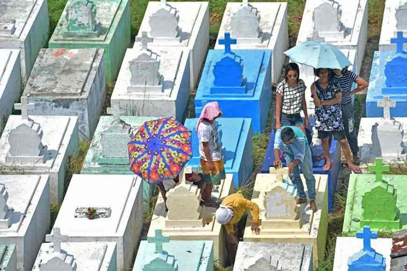 DAVAO. Gipaspasan og limpyo sa duha ka lalaki ang usa ka nitso sulod sa Roman Catholic Cemetery sa Davao City tungod sa kainit sa panahon samtang naghulat ang mga hingtungdan kon kanus-a mahuman ang pagpamintura. (Macky Lim)