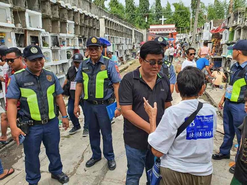 INSPECTION. After visiting the graves of his parents at the Queen City Memorial Gardens, Cebu City Mayor Edgardo Labella (second from right) visits several public cemeteries, including the Carreta Cemetery (above), where he talked to visitors and deployed police officers about the peace and order situation. (SunStar Photo/Arni Aclao)