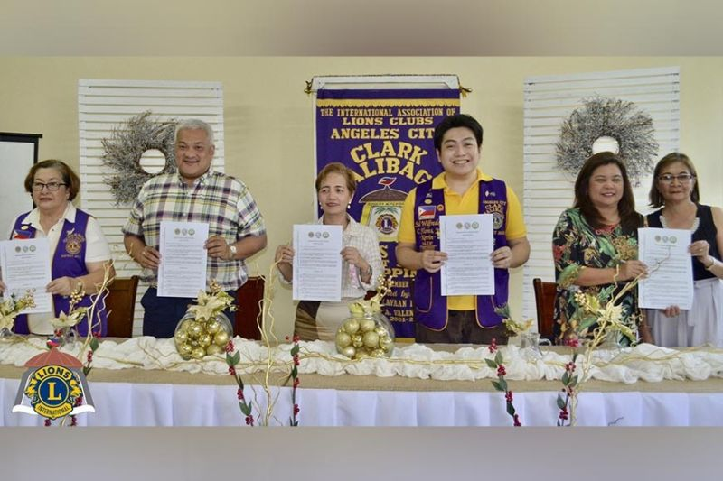 """CITY OF SAN FERNANDO. Mayor Carmelo Lazatin Jr., outgoing Department of Education (DepEd) Superintendent Leilani Cunanan, and Lions Club president Sol Flores Jr. sign the memorandum of understanding to deliver """"Sight for Kids"""" in Angeles City. Flanking them are Lions former governor Imelda Flores, DepEd assistant superintendent Celina Vega, and Pampanga Elementary School principal Emelita Gomez. (Contributed photo)"""