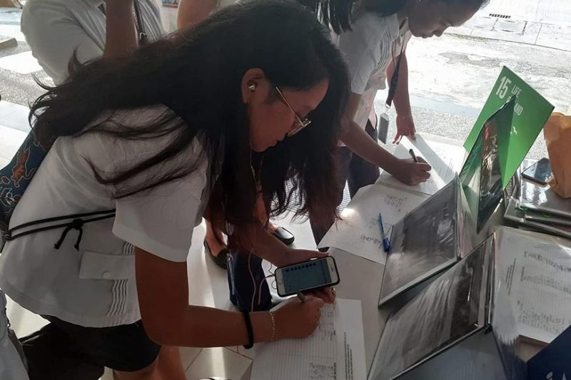 Students of Carlos Hilado Memorial State College in Talisay City sign the petition calling to demolish illegal structures at the Northern Negros Natural Park at the campus recently. (Contributed photo)