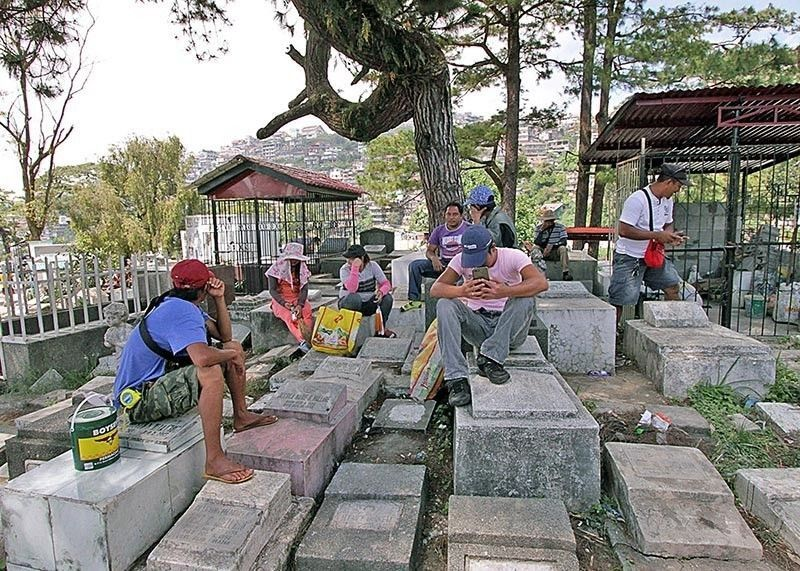 BAGUIO. In this photo taken on October 29, 2019, men and women cleaning the graves of their departed loved ones take a break. (SunStar Baguio File Photo)