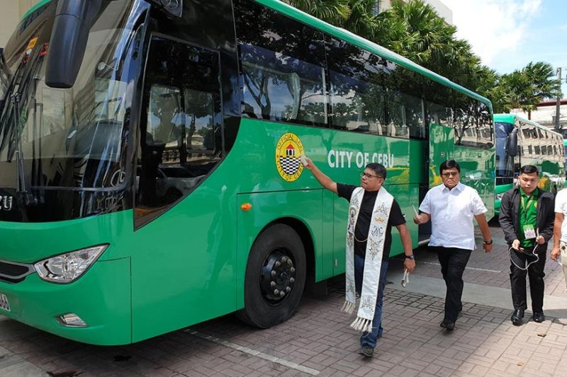 NOT GOING tO THE MOUNTAIN: Cebu City Mayor Edgardo Labella accompanies Fr. Andres Guban as the latter blesses the new buses delivered by RDAK Transport Equipment  Inc. to the Cebu City Government. The buses will no longer be used to transport students in the mountain barangays as originally intended. (Photo by Philip Cerojano)