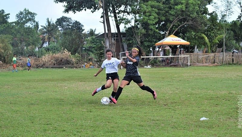 DAVAO. An RMC Solido-JT's Manukan player battles for the ball against a Dolores Football Club (FC) player during their 16th Acosta Cup Ladies Open Football Tournament game held over the weekend at Davao City-UP Sports Complex. (Acosta Cup Facebook)